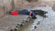 Sıcaktan bunalan küçük kız yol kenarında serinledi