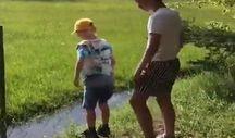 Erkek kardeşin su birikintisinden geçmesine yardım etmek