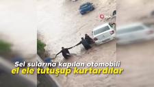 Sel sularına kapılan otomobili el ele tutuşup kurtardılar