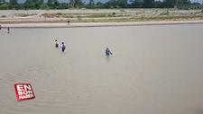 Okula ulaşmak için nehirden geçen öğrenciler